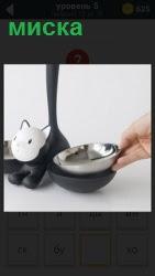 на полу стоит миска и игрушка кошки с высоко поднятым хвостом