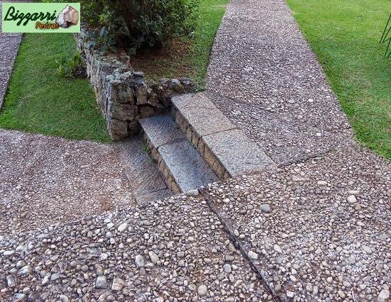 Execução do caminho de pedra com pedregulho do rio, as escadas de pedra folheta com os muros de pedra com o gramado de grama esmeralda.