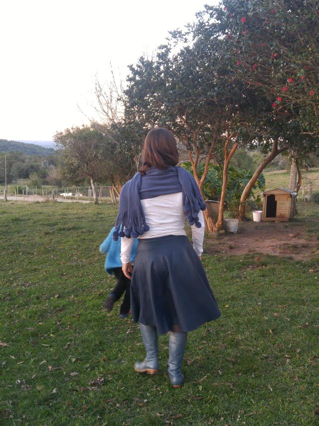 Saia de couro azul, bota de montaria azul, blusa branca e echarpe azul