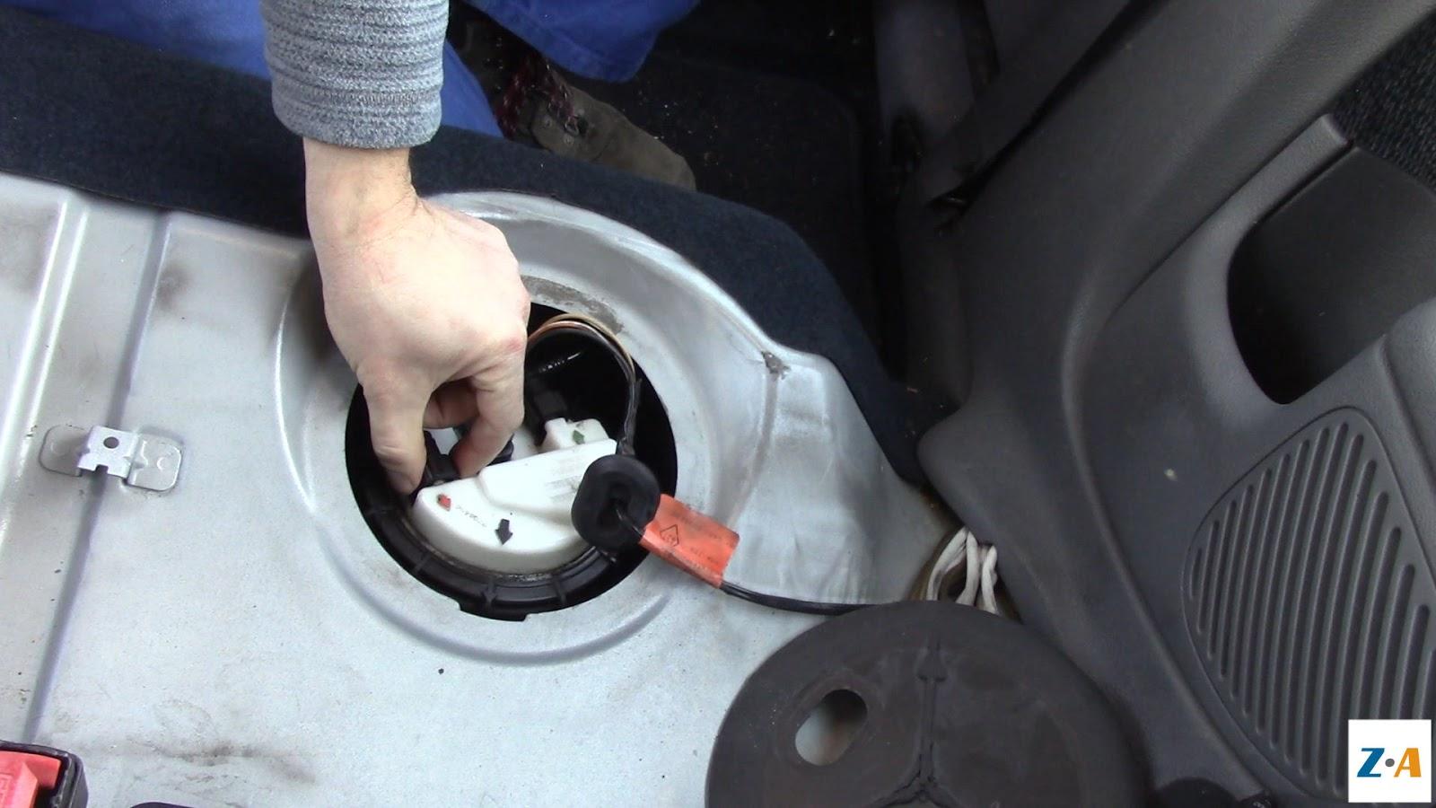 Appuyer de part et d'autre des prises des tuyaux de carburant pour les débrancher.