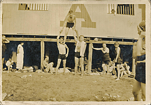 Three unidenified young men entertain beach goers by making a human pyramid. 1920's? From album owned by Estelle Karvoius. Privately held by E. Ackermann, 2016.
