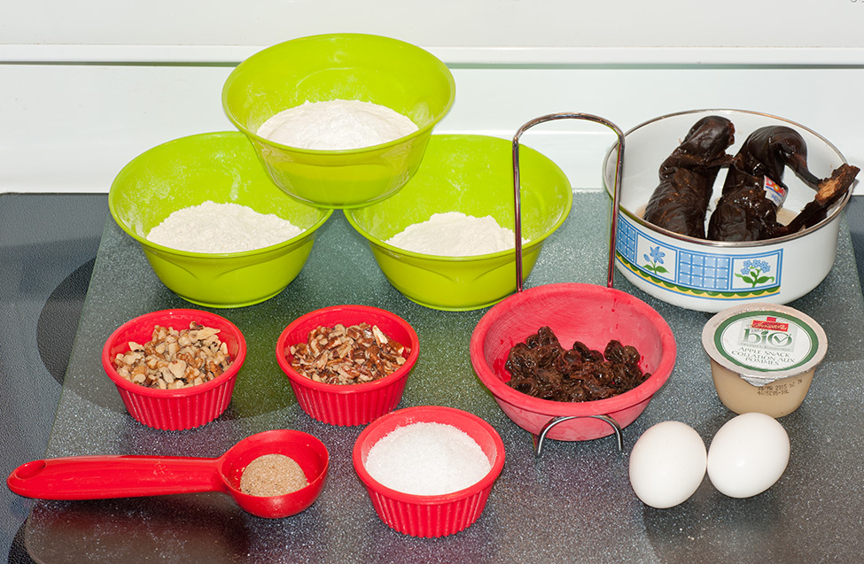 Bows of different types of flour, small ramekins with nuts, eggs and other baking ingredients in green and red bowls.