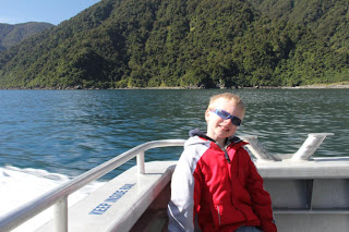 boy on a boat with trees in the background