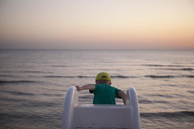 podróże z dzieckiem, wakacje z dzieckiem, chłopiec i morze, zabawa