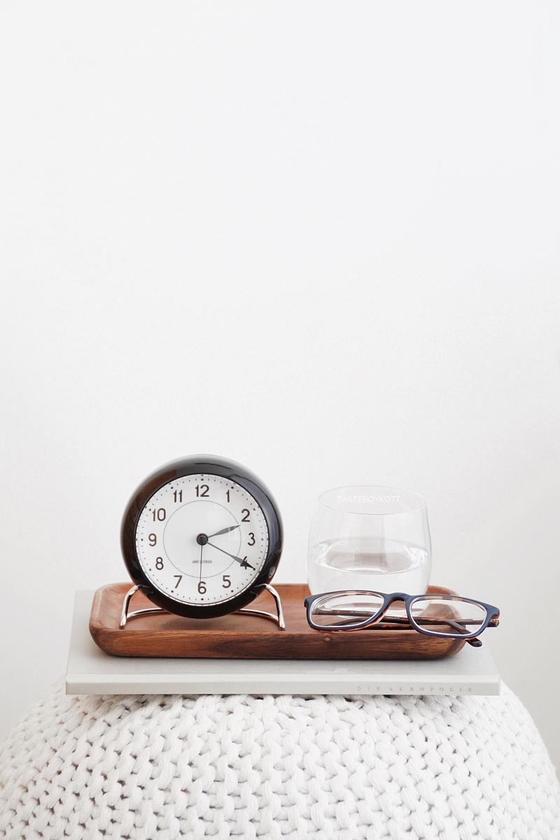 Arne Jacobsen Tischuhr/ Wecker schwarz von Rosendhal, weißer Strickpouf als Nachttisch
