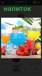 На столе стоят стаканы с напитками разного цвета, оформленные цветами вокруг напитков