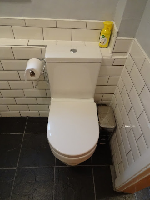 Toilet with White Metro Tiles and Black Floor