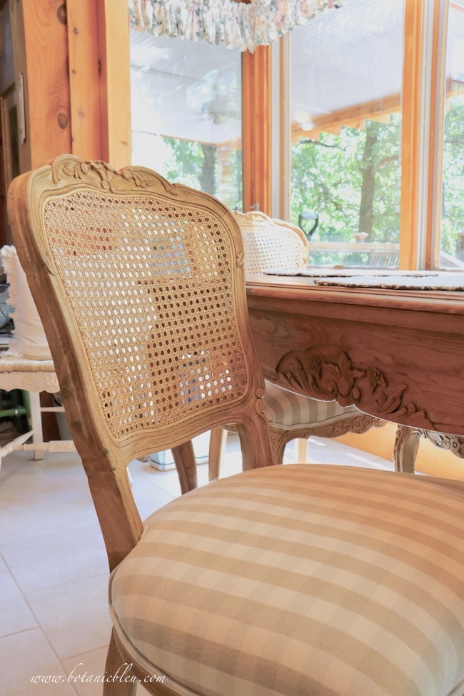 French Country cane back dining chair with carved wood antique French table