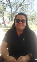 A lady with long brown hair wearing sunglasses and a black shirt. Andrea from Purchasing.
