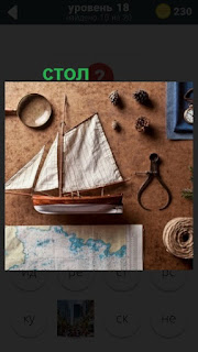 на столе лежат макет яхты и карта с приборами