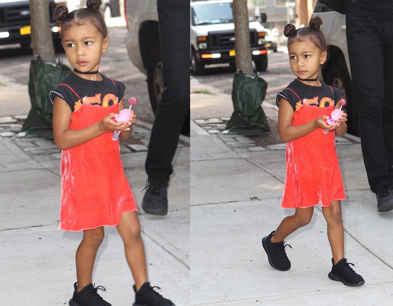 Adorable baby North West and her lollipop during family outing...