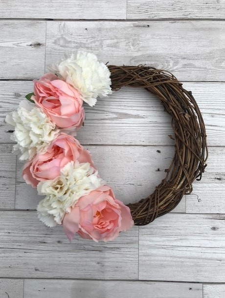 Rattan wreath with pink and white flowers down one side