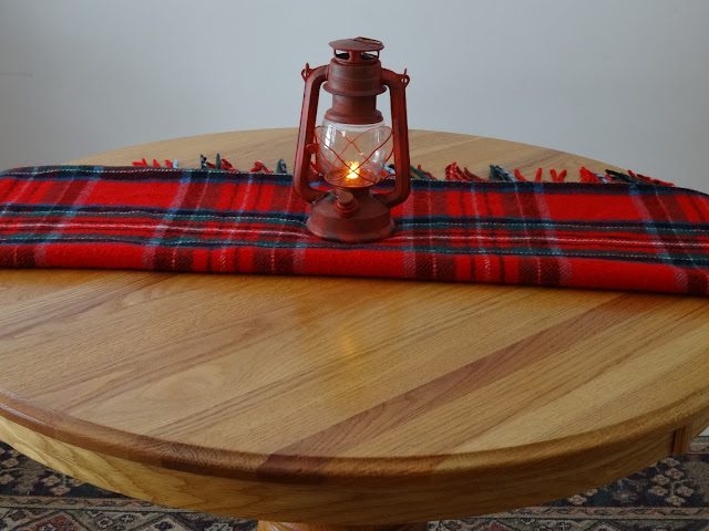 Folded red plaid scarf with lantern.