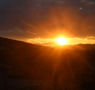 Sun sets below a dark raft of cloud