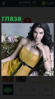 На кресле сидит одинокая девушка в желтом платье с длинными черными распущенными волосами и крупными глазами