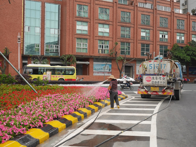 man watering flowers with hose connected to a water truck