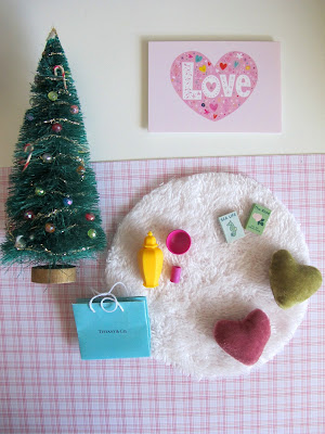 Selection of modern miniature dolls' house accessories in shades of pink, green and white.