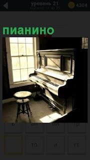 Около окна стоит пианино на которое падает солнечные лучи и рядом стоит стул для музыканта