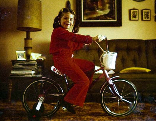image of me sitting on a bike with training wheels in my parents' living room when I am 6 years old; I'm wearing a red bell-bottomed jumpsuit and my hair is in pigtails and I am smiling at the camera with missing front teeth