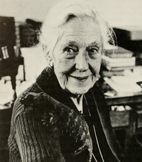 Doris Holmes Blake at her desk with her pet lizard on her shoulder