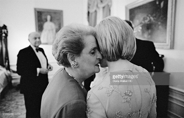 black and white image of Madeleine Albright whispering in Hillary Clinton's ear at a state dinner in 1998