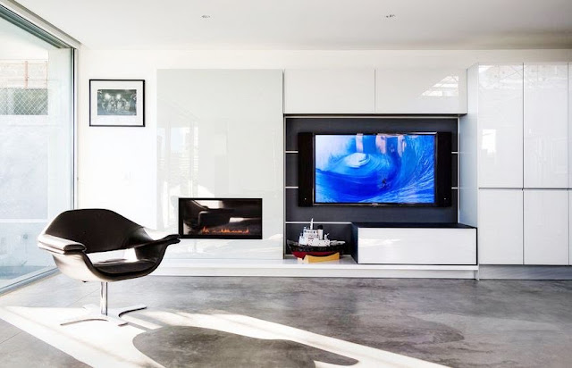 Modern family room in the Flip Flop House with glass flat front cabinetry around the television and grey floor