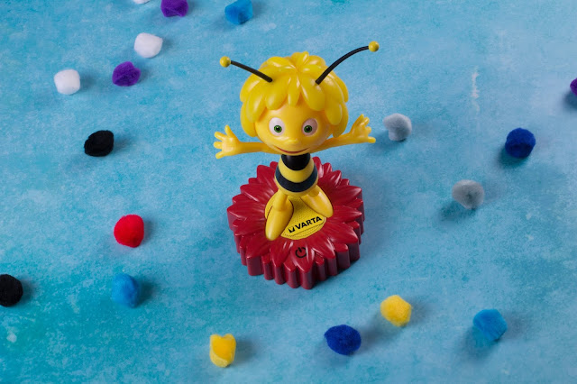 A plastic maya the bee character, standing on a red flower