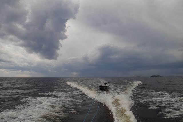 Narun päässä vedetään pikkuvenettä merellä, taivaalla on uhkaavat mustat pilvet