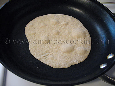 A close up photo of a low fat homemade tortilla being cooked in a skillet.