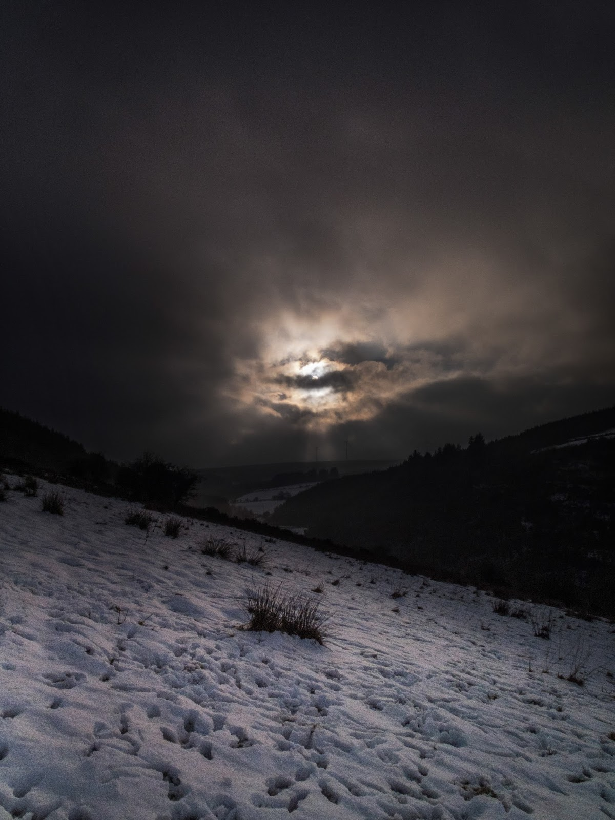 Snow covered mountain side with sun glowing behind dark skies emitting sun rays.