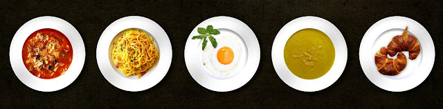 Five white plates with different meals