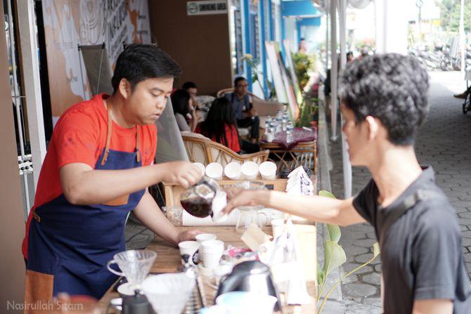 Seorang Barista menuangkan kopi pada pengunjung