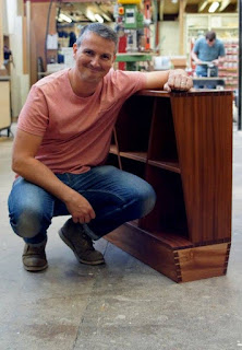 A happy man on his haunches next to a cabinet that he made.