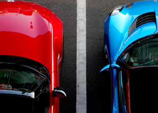 Red car and blue car parked in side by side in parking bays