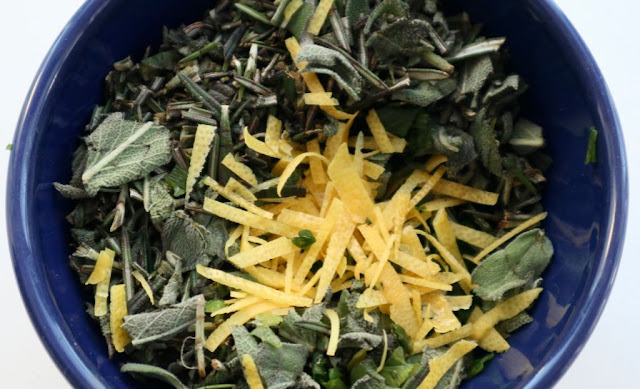 rosemary, sage, lemon zest in a dark blue bowl