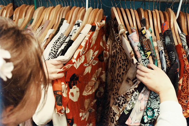 woman searching through a clothing rack