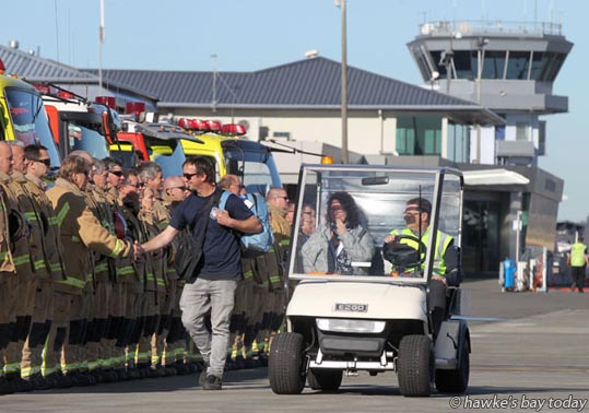 L-R: Matt Tims, Bill's son, Natalie Tims - Firefighters formed a guard of honour as Natalie Tims arrived in a cart after arriving on a commercial flight - The body of former Haumoana volunteer fire chief Bill Tims was brought back to Hawke's Bay Airport, Napier. Mr Tims was killed and his wife Natalie Tims was seriously injured  when they were struck by a motorcycle in downtown San Francisco, USA. photograph
