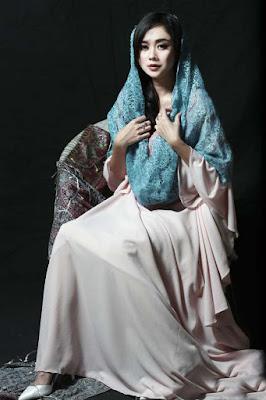 Aura Kasih Tampil Cantik dengan Kerudung Biru duduk di kursi