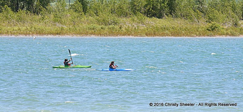 Artist's two teens kayak over the mild white caps on the lake.