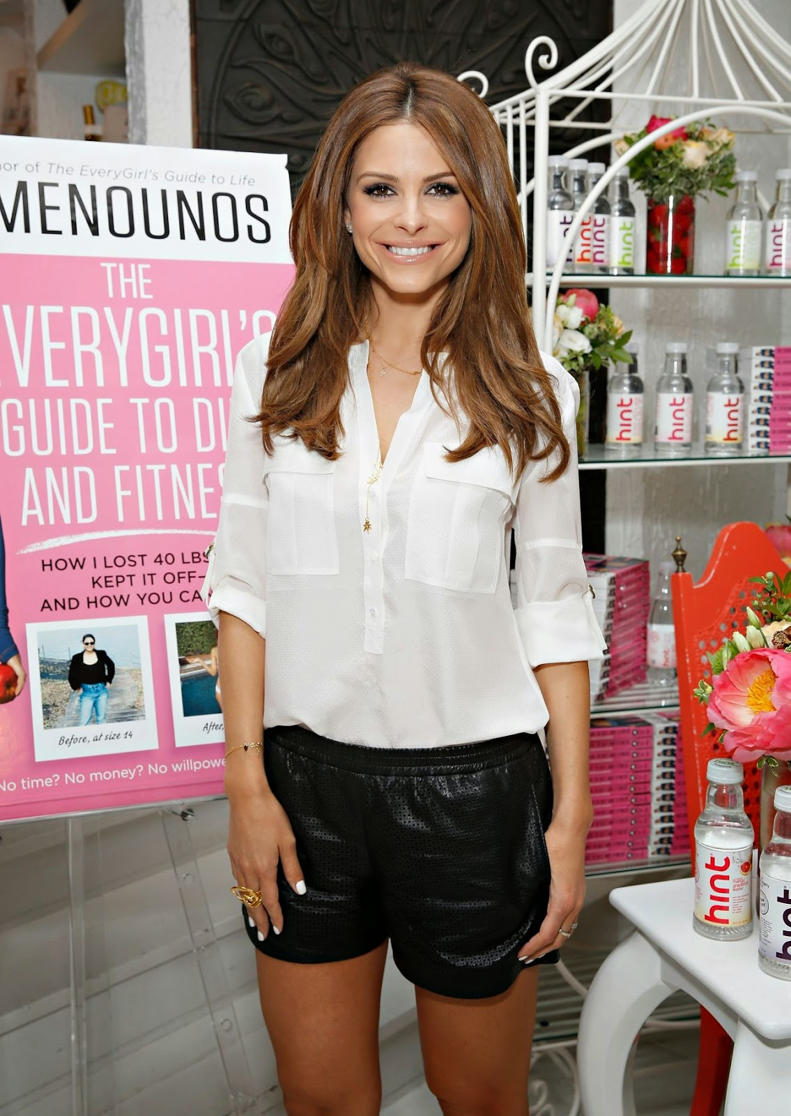 Maria Menounos celebrates the launch of her new book in black shorts and a white blouse in NYC
