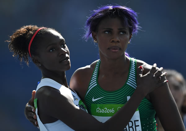 Britain's Dina Asher-Smith and Nigeria's Blessing Okagbare react after competing in the Women's 200m Round 1 at the 2016 Olympics.
