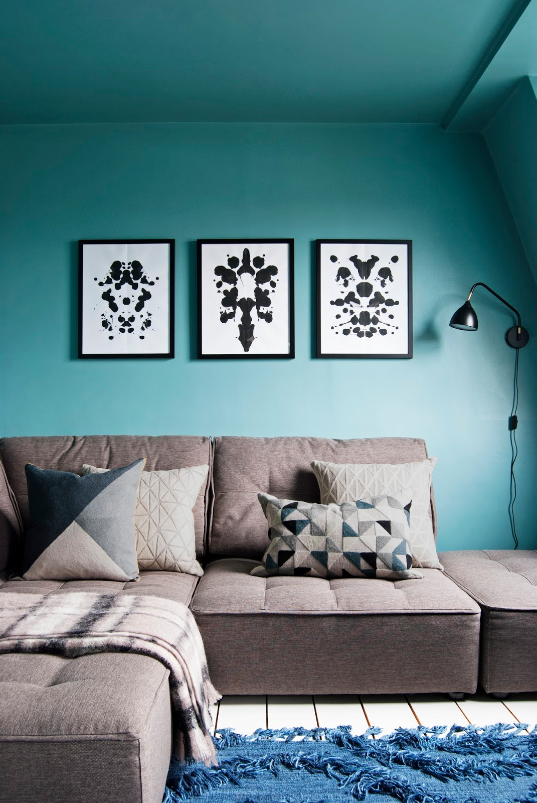 Amara Shoppable Home Inspiration Pages - French For Pineapple Blog - teal blue living tv room with brown sofa and geometric cushions and blue rug
