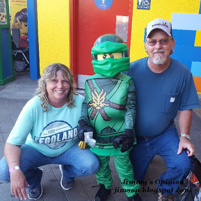 My wife Cindy and I kneeling with our Grandson Benjamin dressed as Lego character Lloyd stainding between us.