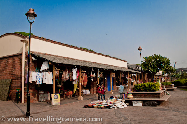 Dilli Haat at Pitampura is one of the places for shopping but not as popular as other Dilli Haat at INA. Some time back we visited Pitampura Dilli Haat, which is near to Netaji Subhash Metro Station. From Metro stop, there is hardly 10 minutes walk to Dilli Haat. Dilli-Haat is not just a market place, but it has been visualized as a showpiece of traditional Indian culture and a forum where rural life & folk art are brought closer to an urban clientele. There is an entry ticket at this Dilli Haat as well, but I think it was less than what we pay at INA. Market inside Pitampura Dilli-Haat is not as glamorous as we have near INA Market. Although it was weekend but there were very few people around this place.As we say - First Impression is last Impression, I was not hopeful about this Dilli Haat anymore. After entering into the first shop, I asked about their business scenario and most of them were very positive about it, although we failed to notice the evidence...There are some shops offering decorative stuff for homes, ethnic cloths, sculptures, art-pieces, Artificial Jewellery etc... Overall it's a colorful market, but many shops in this complex are empty, while many stalls in INA are installed outside concrete shops. The landscaping of the area incorporates colorful flowering and trees...Dilli Haat at Pitampura is well planned and beautifully built. It looks amazing during evening when all lights are ON. Metro-train gives best view of this Dilli Haat in Pitampura region !!!Stuff available in these markets is usually different and something which is unique in their own style. Various regional specialties are available in these markets. At times things are bit costly, but worth buying.Stall number 34 to 47 are on left :)Colors of this market are different from other markets in Delhi and of-course good space around this market, which is hard to find in other markets like Karol-Bag, Sarojani, Chandni Chowk etc...Somehow this shop had most of the customers and sale was decent !!Since market is comparatively less crowded and huge space around the shops, young couples like this place.Empty shops at Pitampura Dilli Haat !!! There were lot more other shops which were not occupied...There is a huge area which is normally used for various functions and government activities. Delhi Tourism was organizing something something on that day. There was something in evening and seemed like some musical performances, as some of the folks were practicing with appropriate sound level on different mics.There is a specific area dedicated for food court. Variety of snacks are available and probably food shops had more sale than other shops selling cloths & decorative stuff etc.Ticket Counter of Pitampura Dilli Haat !!!More details about Dilli Haat can be found at http://delhitourism.nic.in/delhitourism/tourist_place/dilli_haat.jsp