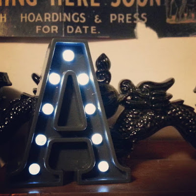 Miniature light-up marquee letter.