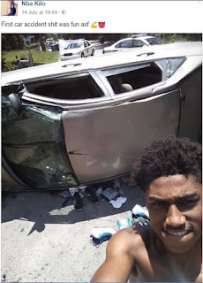 Man taking a selfie infront of his wrecked car