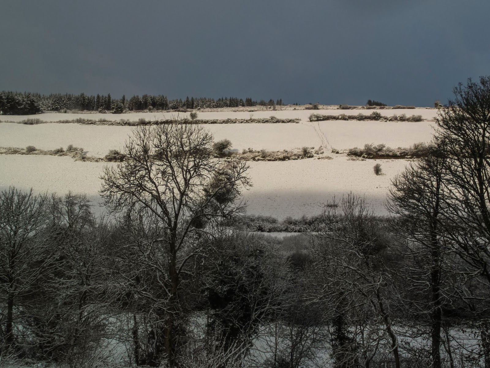 Dark sky above a snow covered mountainside in North County Cork.