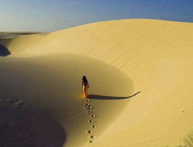 woman walking across desert sand dunes, with Jackson Kiddard quote