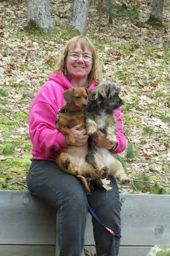 woman holding two small dogs
