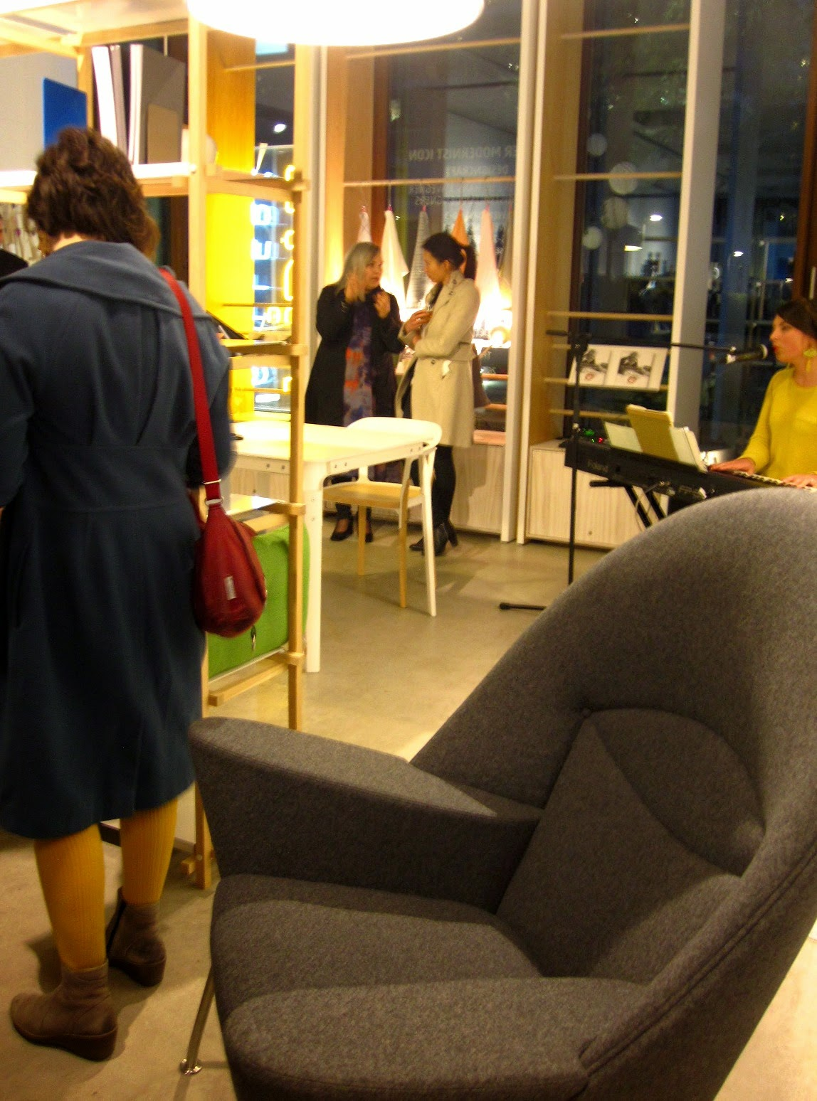 An exhibition space with an armchair and table and chair on display. A musician sings and plays keyboard in the corner.
